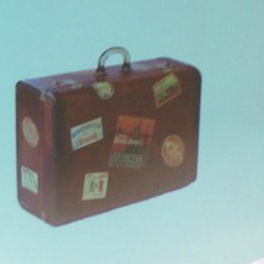 photo from a lecture slide: old brown suitcase with stickers from around the world